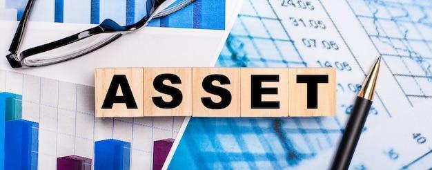 Na jasnych schematach okulary, długopis i drewniane kostki z napisem asset. pomysł na biznes.