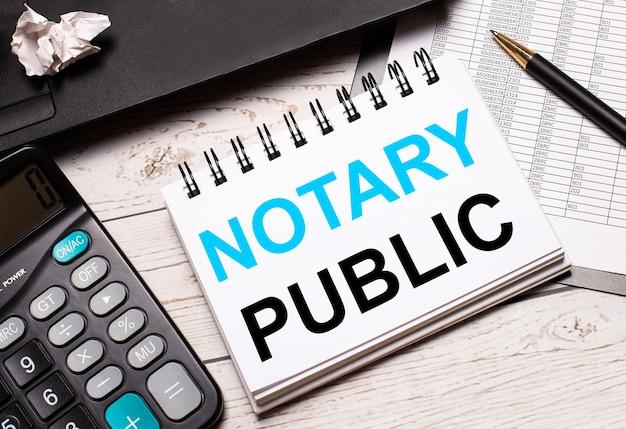 Na jasnym biurowym stole stoi komputer, czarny kalkulator, długopis i notes z napisem notary public. pomysł na biznes.