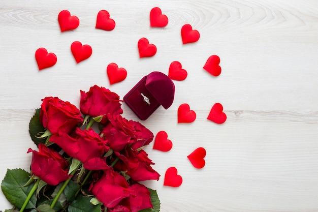 Na jasnym drewnianym stole czerwone róże, dekoracje w formie serc i pierścionek zaręczynowy