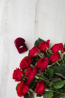 Na jasnym drewnianym stole, czerwonych różach i pierścionku zaręczynowym