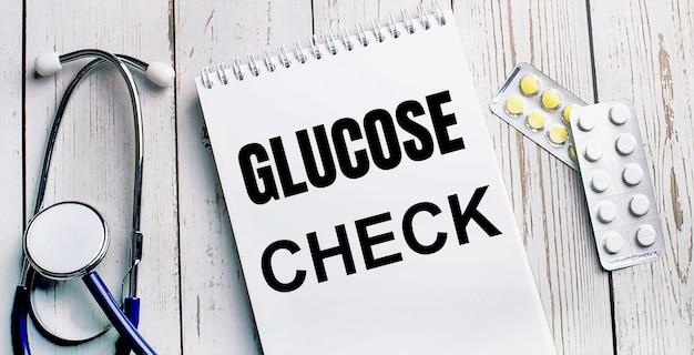 Na jasnym drewnianym stole leżą stetoskop, pigułki i notes z napisem glucose check. koncepcja medyczna