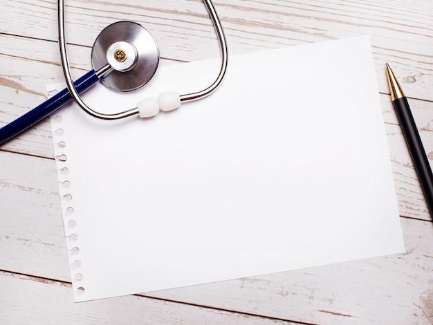 Na jasnym drewnianym stole leży stetoskop, długopis i kartka z miejscem na wpisanie tekstu. koncepcja medyczna