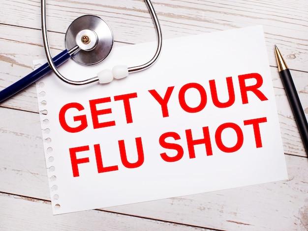 Na jasnym drewnianym stole leży stetoskop, długopis i kartka z napisem get your flu shot. koncepcja medyczna