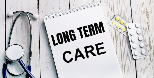 Na jasnym drewnianym stole leży stetoskop, tabletki i notes z napisem long term care