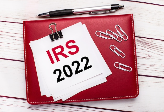 Na jasnym drewnianym tle bordowy długopis i notatnik. na zeszycie znajdują się białe spinacze oraz biała kartka z napisem irs 2022 irs internal revenue service. pomysł na biznes