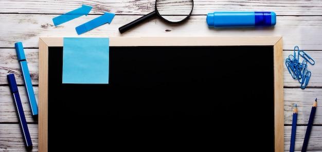 Na jasnym drewnianym tle, czarna tablica z napisami, niebieskie i jasnoniebieskie markery, długopisy i ołówki, lupa i spinacze z naklejkami. umieść, aby wstawić tekst.