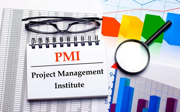 Na jasnym drewnianym tle jasne, wielokolorowe naklejki z napisem pmi project management institute
