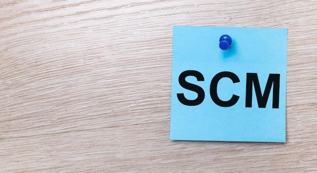 Na jasnym drewnianym tle - jasnoniebieska kwadratowa naklejka z tekstem scm supply chain management