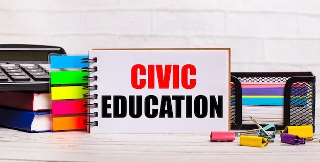 Na jasnym drewnianym tle kalkulator, różnokolorowe patyczki i notes z napisem edukacja obywatelska. pomysł na biznes