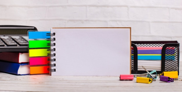 Na jasnym drewnianym tle kalkulator, różnokolorowe patyczki i pusty zeszyt z miejscem na wpisanie tekstu. szablon. pomysł na biznes