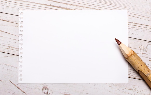 Na jasnym drewnianym tle kredka i biała pusta kartka papieru z miejscem na wstawienie tekstu. szablon