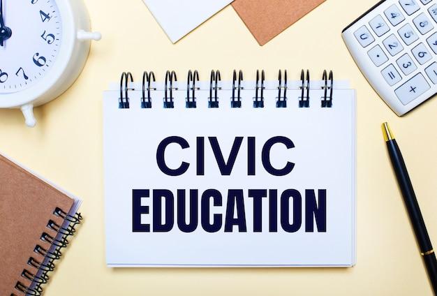 Na jasnym tle biały budzik, kalkulator, długopis i notes z napisem edukacja obywatelska. płaskie ułożenie