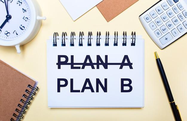 Na jasnym tle biały budzik, kalkulator, długopis i notes z napisem plan b