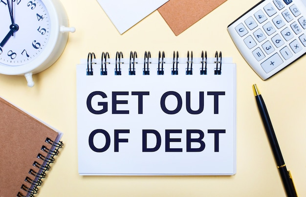 Na jasnym tle biały budzik, kalkulator, długopis i notes z napisem wypuść z długu. płaskie ułożenie