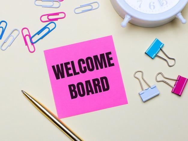 Na jasnym tle biały budzik, różowe, niebiesko-białe spinacze, złoty długopis i różowa naklejka z napisem welcome board