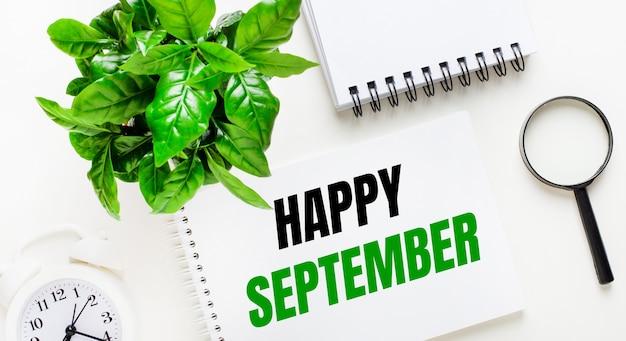 Na jasnym tle biały budzik, szkło powiększające, zielona roślina i notes z napisem happy september.