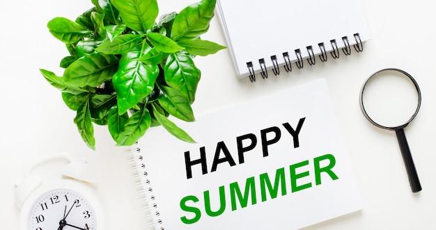 Na jasnym tle biały budzik, szkło powiększające, zielona roślina i notes z napisem happy summer.