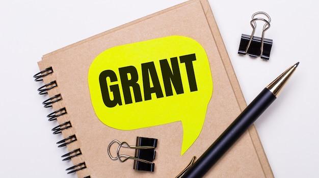 Na jasnym tle brązowy zeszyt, czarny długopis i spinacze oraz żółta kartka z napisem grant. pomysł na biznes.
