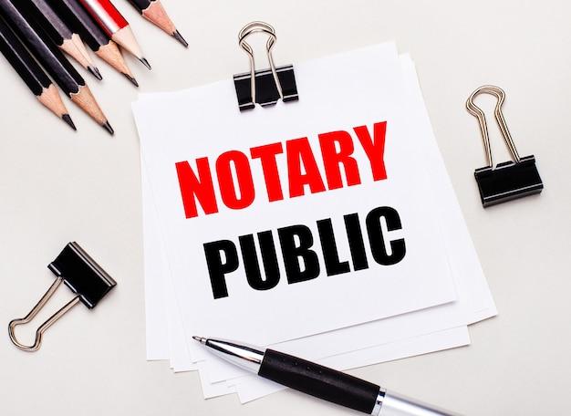 Na jasnym tle czarne ołówki, czarne spinacze, długopis i kartka białego papieru z napisem notary public.