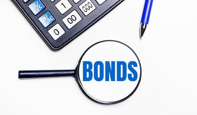 Na jasnym tle czarny kalkulator, niebieski długopis i lupa z tekstem wewnątrz obligacji.