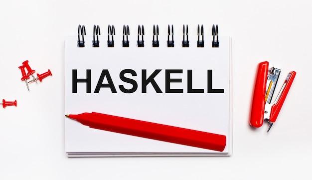 Na jasnym tle czerwony długopis, czerwony zszywacz, czerwone spinacze i notes z napisem haskell