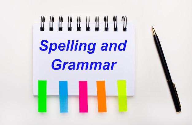 Na jasnym tle długopis, zeszyt z napisem pisownia i gramatyka oraz jasne naklejki.