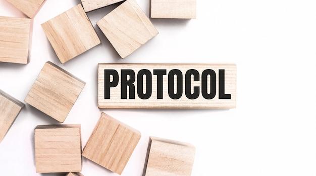 Na jasnym tle drewniane kostki i drewniany klocek z napisem protocol. widok z góry