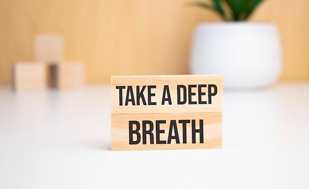 Na jasnym tle drewniane kostki i drewniany klocek z tekstem weź głęboki oddech. widok z góry