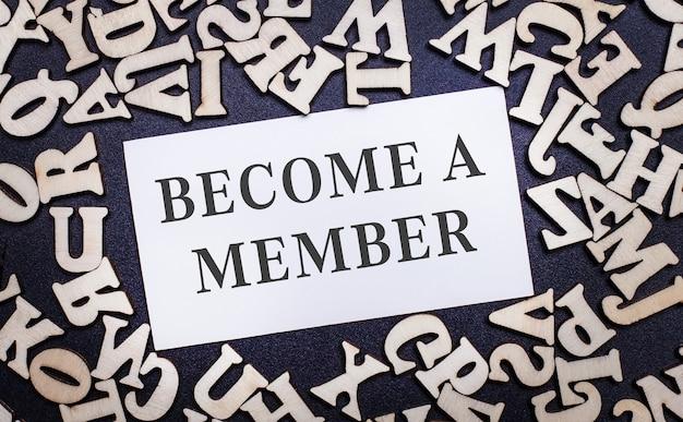 Na jasnym tle drewniane litery alfabetu angielskiego, aw środku biała kartka z napisem become a member