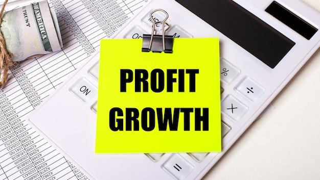 Na jasnym tle - gotówka, biały kalkulator i żółta naklejka pod czarnym spinaczem z napisem profit wzrost. pomysł na biznes