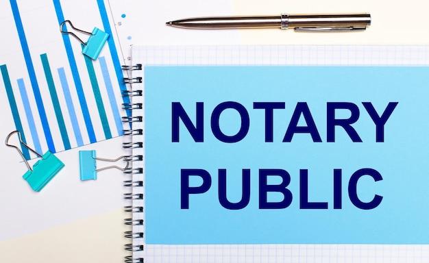 Na jasnym tle - jasnoniebieskie schematy, spinacze i kartka z napisem notary public. widok z góry. pomysł na biznes