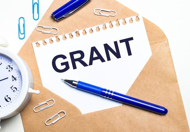 Na jasnym tle koperta kraftowa, budzik, spinacze, niebieski długopis i kartka z napisem grant.
