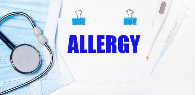 Na jasnym tle leżą stetoskop, elektroniczny termometr, strzykawka, maska na twarz i kartka papieru z napisem alergia. koncepcja medyczna