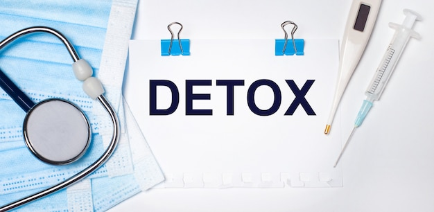 Na jasnym tle leżą stetoskop, elektroniczny termometr, strzykawka, maska na twarz i kartka papieru z napisem detox. koncepcja medyczna