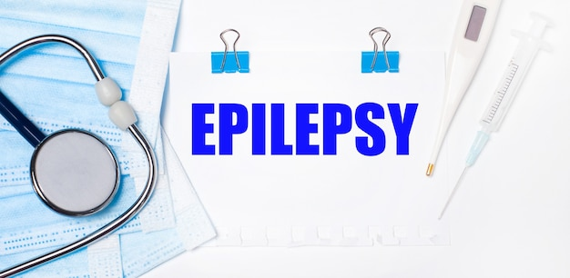 Na jasnym tle leżą stetoskop, elektroniczny termometr, strzykawka, maska na twarz i kartka papieru z napisem epilepsy. koncepcja medyczna