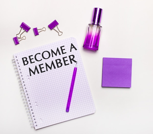 Na jasnym tle liliowy prezent, perfumy, liliowe dodatki biznesowe i notes z liliowym napisem zostań członkiem