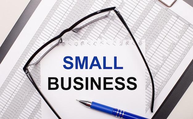 Na jasnym tle raport, okulary w czarnych oprawkach, długopis i kartka z napisem small business. pomysł na biznes