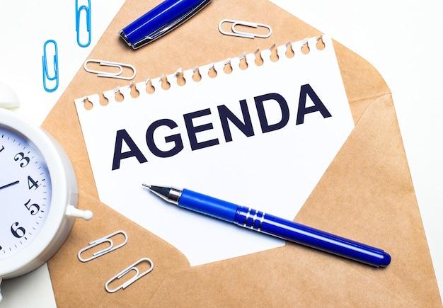 Na jasnym tle rzemieślnicza koperta, budzik, spinacze, niebieski długopis i kartka z napisem agenda.