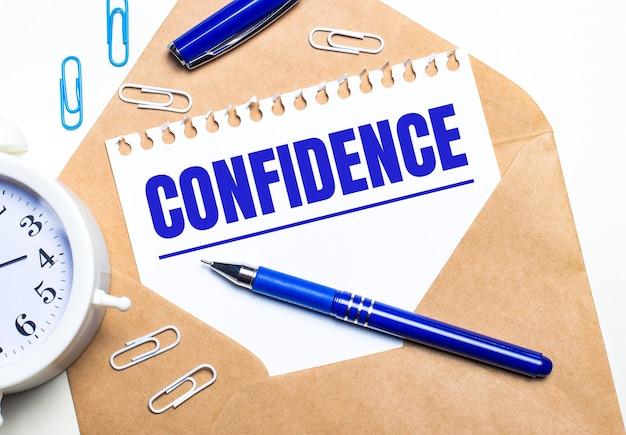 Na jasnym tle rzemieślnicza koperta, budzik, spinacze, niebieski długopis i kartka z napisem confidence.