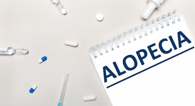 Na jasnym tle strzykawka, stetoskop, fiolki z lekarstwami, ampułka i biały notatnik z napisem alopecia. koncepcja medyczna