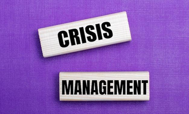 Na jasnym tle w kolorze liliowym jasne drewniane klocki z napisem crisis management