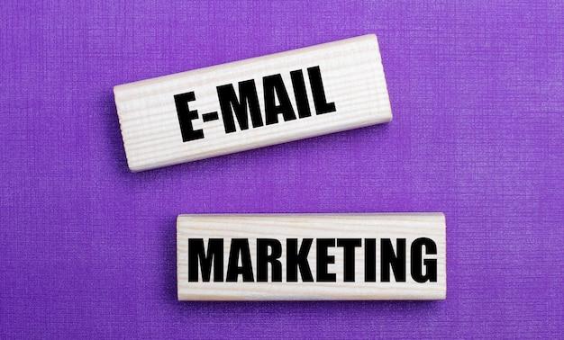 Na jasnym tle w kolorze liliowym, klocki z jasnego drewna z napisem e-mail marketing