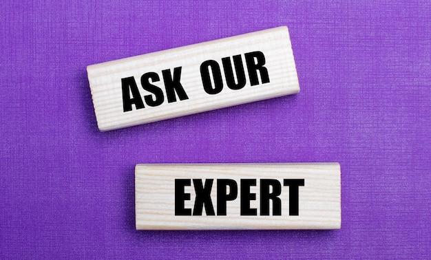 Na jasnym tle w kolorze liliowym klocki z jasnego drewna z napisem zapytaj naszego eksperta