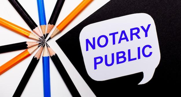 Na jasnym tle wielokolorowe ołówki, a na czarnym tle biała kartka z napisem notary public.
