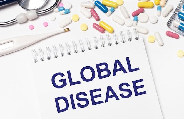 Na jasnym tle wielokolorowe pigułki, stetoskop, termometr elektroniczny i notes z napisem global disease. pojęcie medyczne.