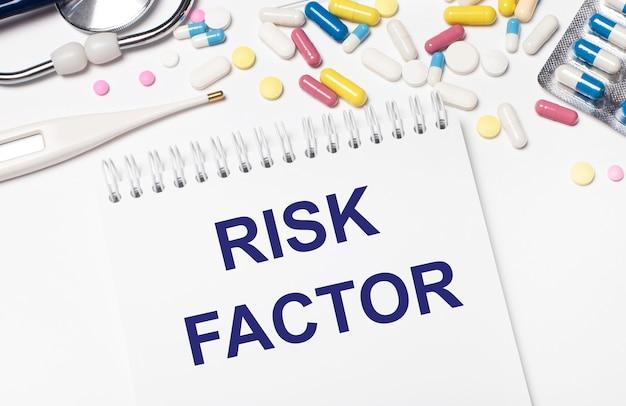 Na jasnym tle wielokolorowe tabletki, stetoskop, termometr elektroniczny i notes z napisem czynnik ryzyka. pojęcie medyczne.