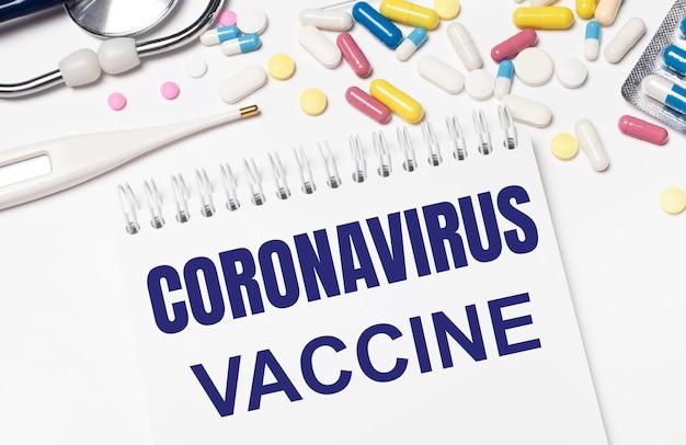 Na jasnym tle wielokolorowe tabletki, stetoskop, termometr elektroniczny i notes z napisem szczepionka koronawirusowa. pojęcie medyczne.