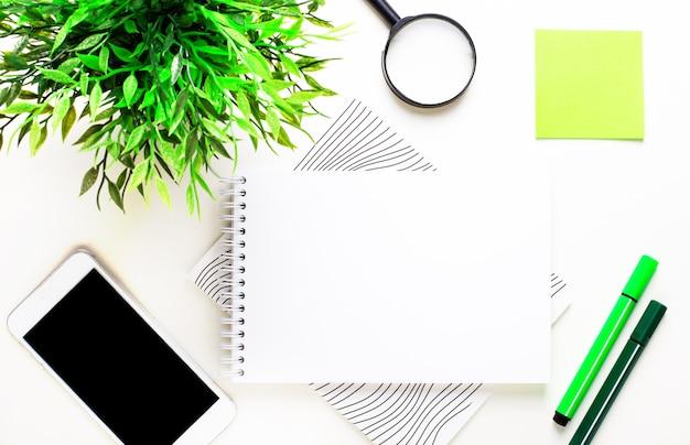 Na jasnym tle zielona roślina, markery, telefon, zielona naklejka i pusty notatnik do wstawiania tekstu lub ilustracji. leżał na płasko