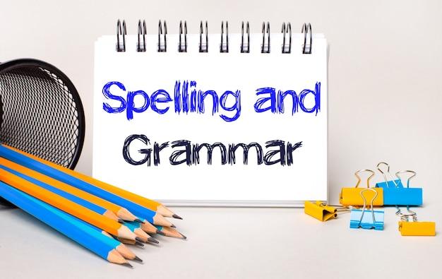 Na jasnym tle żółto-niebieskie ołówki i spinacze do papieru oraz biały zeszyt z napisem pistelstwo i gramatyka