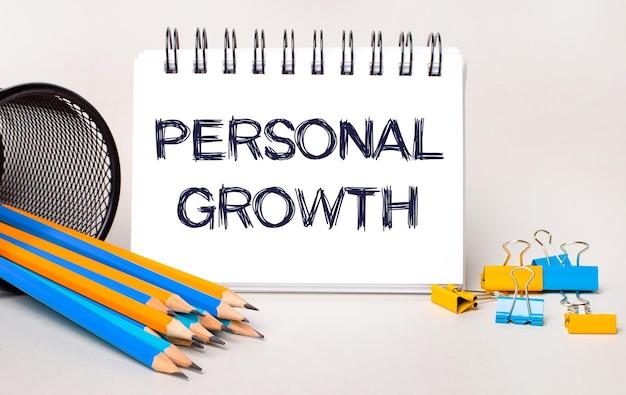 Na jasnym tle żółto-niebieskie ołówki i spinacze oraz biały zeszyt z napisem personal growth